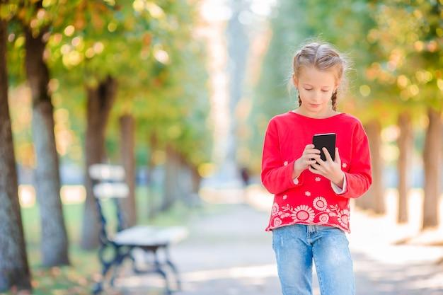 秋にスマートフォンを持つ愛らしい少女。屋外の暖かい晴れた秋の日に楽しんでいる子供