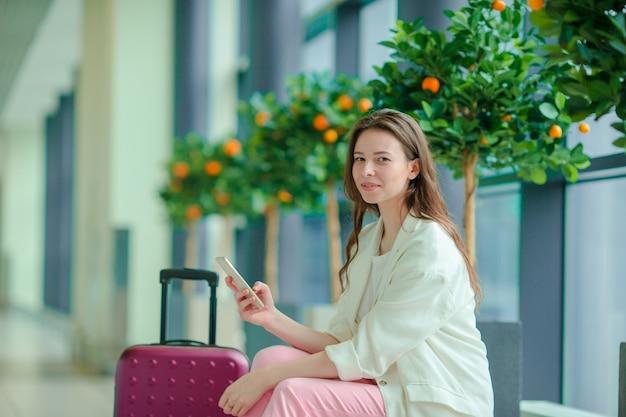 国際空港でスマートフォンを持つ若い女性の肖像画。飛行機を待っている空港ラウンジの航空会社の乗客