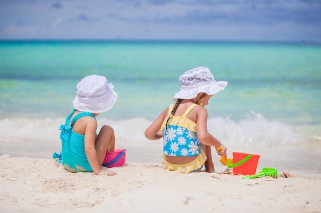 熱帯の休暇中にビーチおもちゃで遊んで幸せな女の子