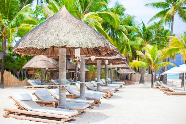 エキゾチックな熱帯の白い砂浜の高級リゾートのビーチベッド