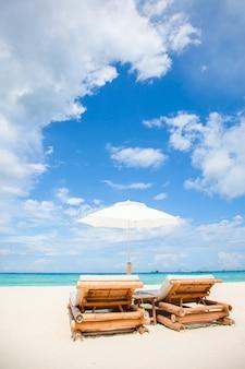 エキゾチックな熱帯の白い砂浜のビーチチェアと傘