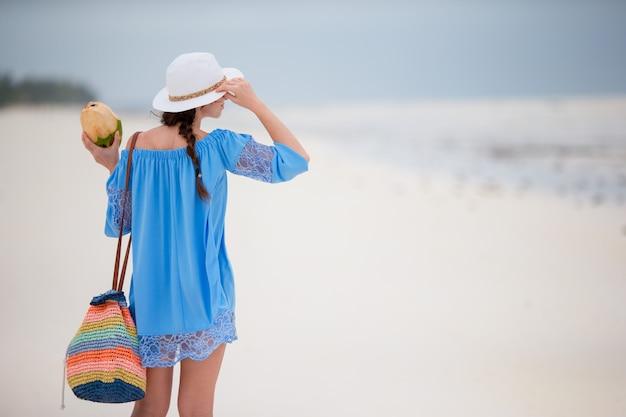 ココナッツを持つ若い女性は、ビーチでの休暇をお楽しみください