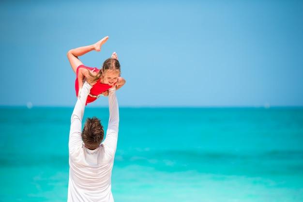 Счастливый отец и маленькая девочка на тропическом пляже