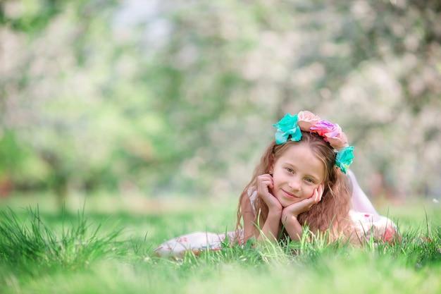 Портрет очаровательны маленькая девочка в цветущий вишневый сад на открытом воздухе
