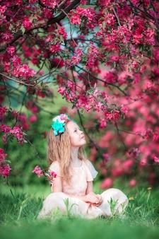 Очаровательны маленькая девочка в красивый цветущий яблоневый сад на открытом воздухе