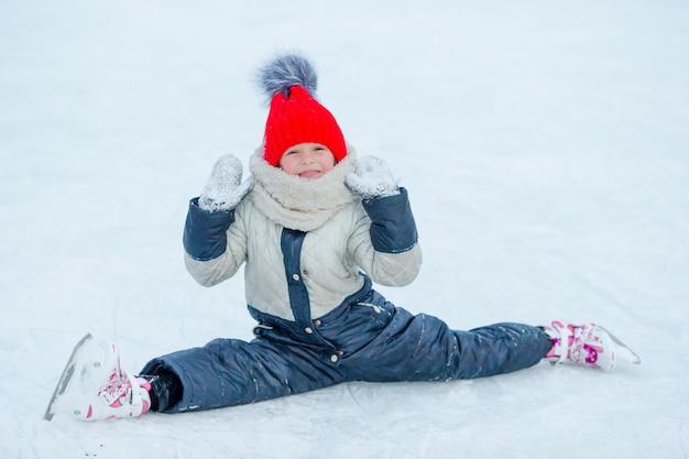 秋の後スケートと氷の上に座っている小さなかわいい女の子