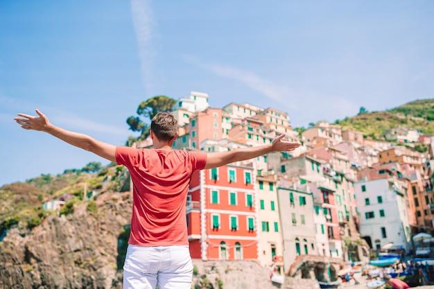 Молодой турист человек с великолепным видом на потрясающую деревню манарола, чинкве-терре, лигурия, италия