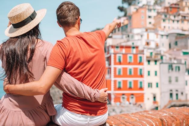 Туристы, глядя на живописный вид риомаджоре, чинкве-терре, лигурия, италия