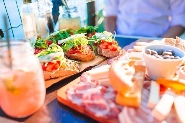 Вкусная итальянская закуска. свежие брускетты, сыры и мясо на доске в кафе с видом в манароле