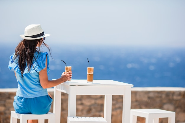 海の景色を楽しみながら冷たいコーヒーを飲む若い女性。美しい女性はフラッペを楽しんでビーチでエキゾチックな休暇中にリラックスします。