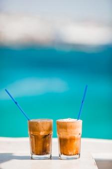 海と木製のテーブルの上のコーヒーカフェラテ