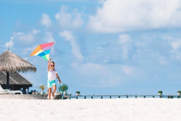Маленькая девочка летает воздушный змей на пляже с бирюзовой водой
