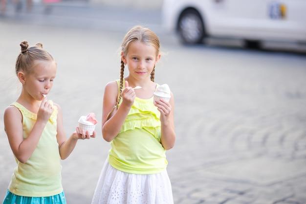 Счастливые маленькие девочки едят мороженое под открытым небом кафе.