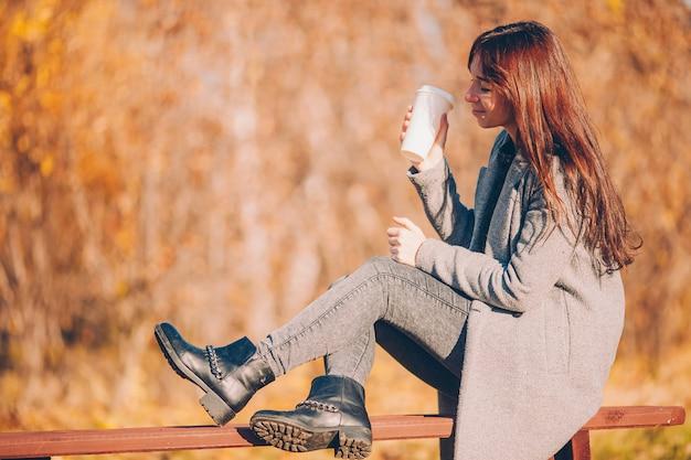 秋コンセプト-秋の紅葉の下で秋の公園でコーヒーを飲んで美しい女性