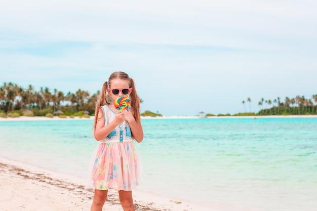 Прелестная маленькая девочка с леденцом на палочке на тропическом пляже