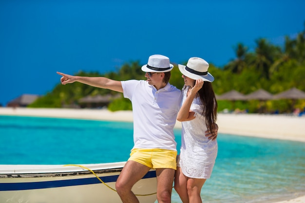 Молодая счастливая пара на белом пляже в летние каникулы
