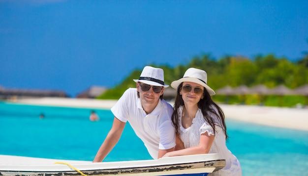 Молодая счастливая семья на белом пляже на летних каникулах