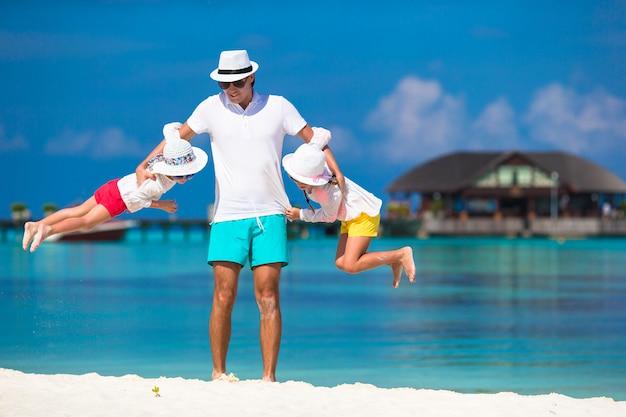Счастливый отец и его очаровательные маленькие дочери на тропическом пляже, с удовольствием