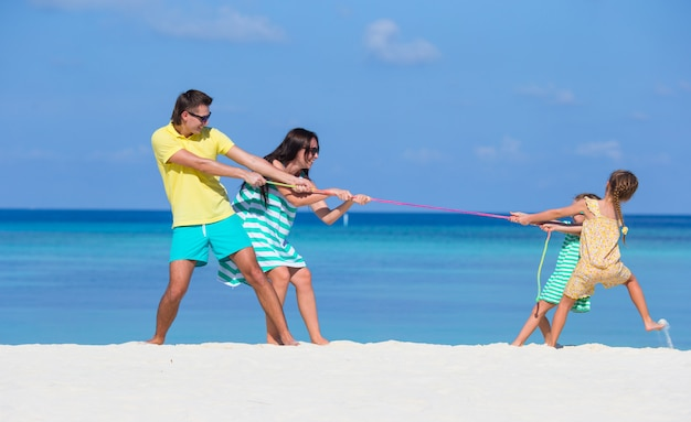 Счастливая семья, играя вместе на белом пляже