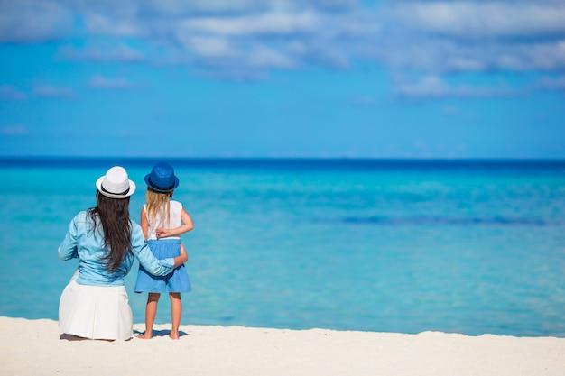 Маленькая девочка и молодая мать во время пляжного отдыха