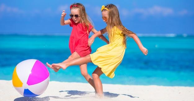 Маленькие очаровательные девочки играют на пляже с воздушным шариком