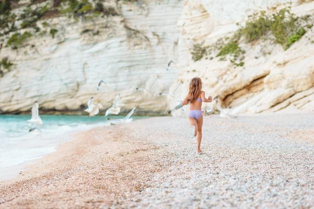 たくさんの楽しみを持っているビーチでアクティブな女の子。海岸でスポーティな演習を行うかわいい子供