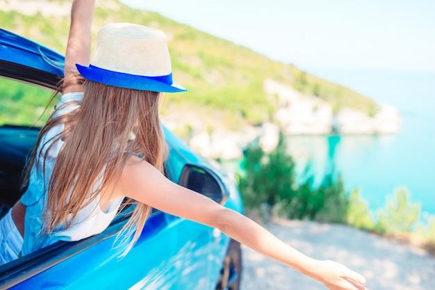 車、美しい風景で休暇旅行の少女