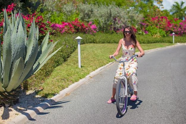 トロピカルリゾートで自転車に乗る若い女性