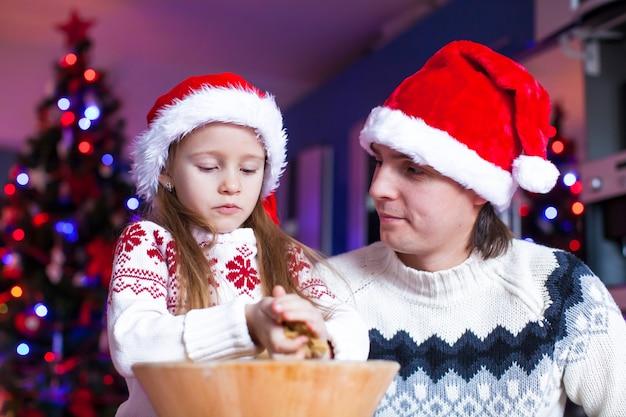 サンタ帽子の小さな娘と若いお父さんジンジャーブレッドクッキーを焼く