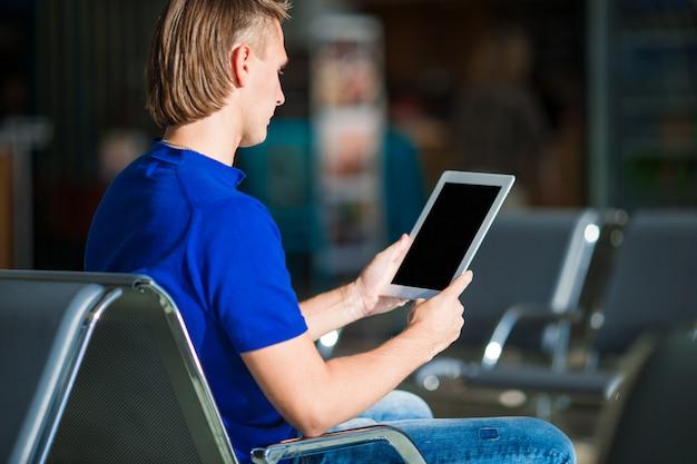 Молодой человек с ноутбуком в аэропорту во время ожидания посадки