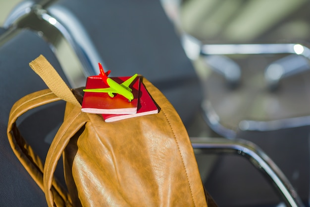 Крупным планом паспорта и модель самолета на рюкзаке в аэропорту
