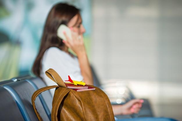 搭乗を待っている間、電話で話している若い女性