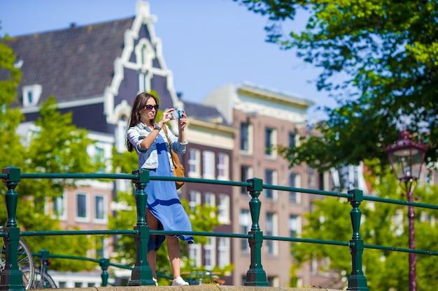 Молодая женщина турист, принимая фото на красивый вид на европейский город с камерой мобильного смартфона