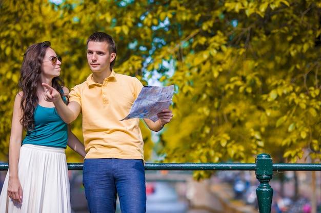 ヨーロッパの都市の地図を見て若い観光客のカップル