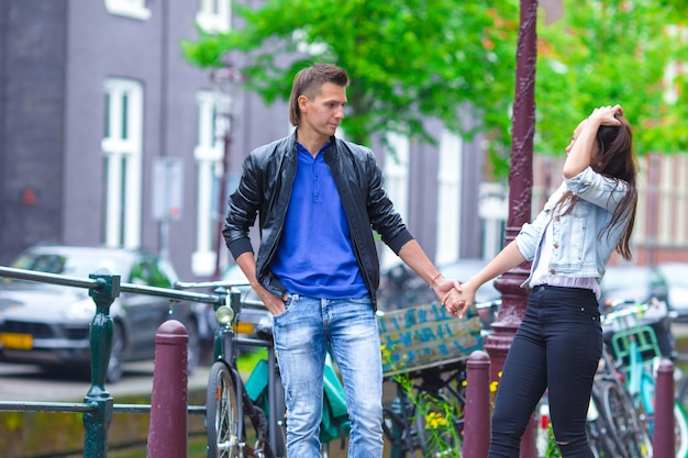 アムステルダム、オランダを訪れるヨーロッパの都市を歩いて恋に幸せなカップル