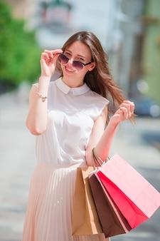 屋外の買い物袋を持つ若い幸せな女の子。笑みを浮かべて買い物袋を持って通りに立っている美しい幸せな女性の肖像画