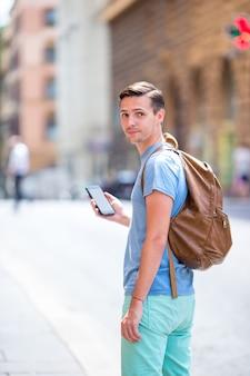 Кавказский турист с смартфон в руках, прогуливаясь по пустынным итальянским улицам в риме. молодой городской мальчик на каникулах исследуя европейский город