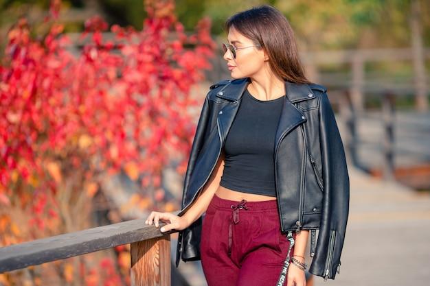秋のコンセプト-秋の紅葉の下で秋の公園でコーヒーを飲みながら美しい女性