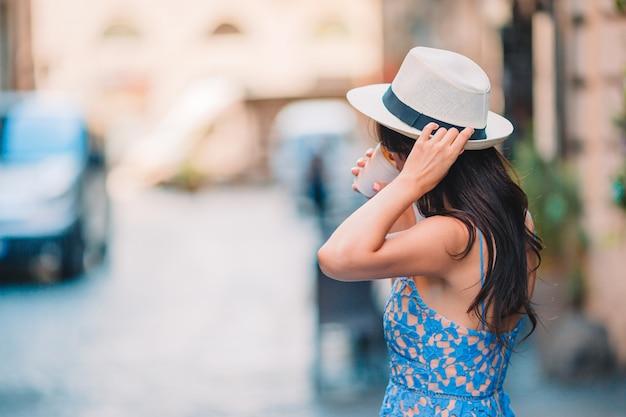 ヨーロッパでコーヒーを飲んで幸せな若い都市女性。白人観光客は空の街で彼女のヨーロッパの休暇を楽しむ