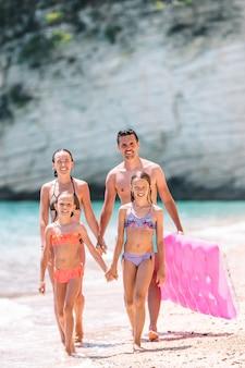 一緒に楽しんで白いビーチで幸せな美しい家族