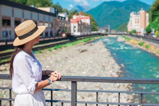 Счастливая девушка в шляпе на набережной горной реки в европейском городе.
