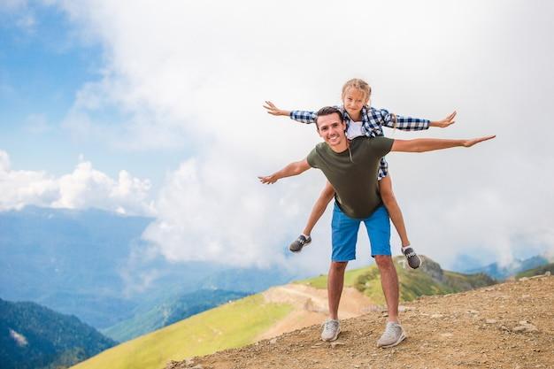 霧の背景の山の美しい幸せな家族
