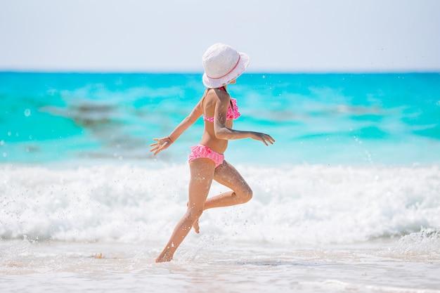 カリブ海の休暇中にビーチを歩いて幸せな少女