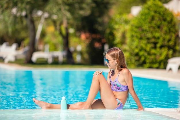 Маленькая девочка с бутылкой солнцезащитного крема, сидя на тропическом пляже
