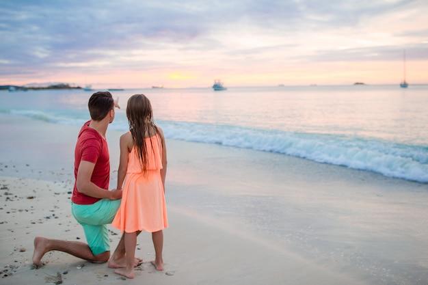 エキゾチックなビーチで夕日を見て彼の小さな子供を持つ若い父親