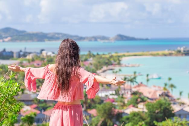 カリブ海の熱帯の島の湾の景色を持つ若い観光客女性