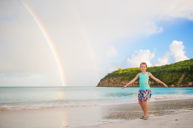 幸せな少女は、海の上の美しい虹を背景にしています。カリブ海のビーチの美しい虹