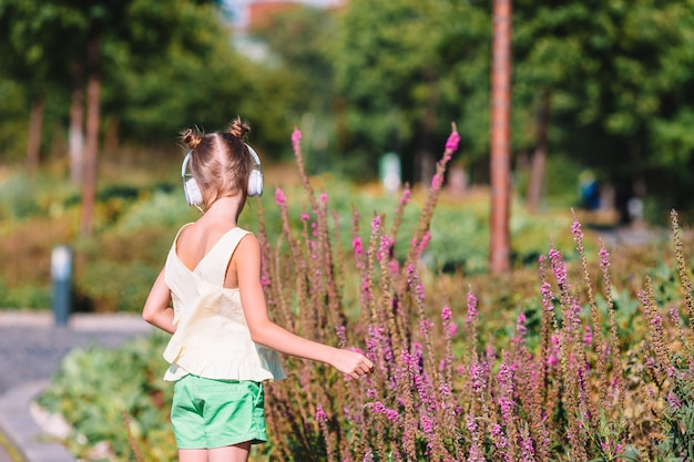 Маленькая прелестная девушка слушает музыку в парке