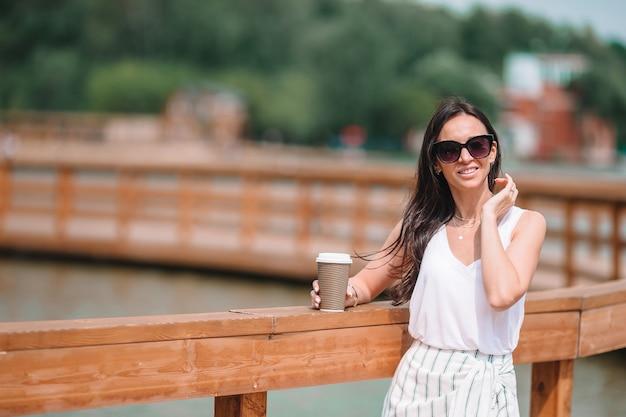 ヨーロッパの都市でコーヒーを飲んで幸せな若い都市女性。