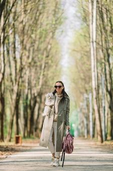 白い犬と一緒に歩く若いスタイリッシュな女性